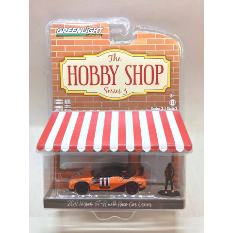 Greenlight - 2011 Nissan GT-R with Race Car Driver Laranja - The Hobby Shop